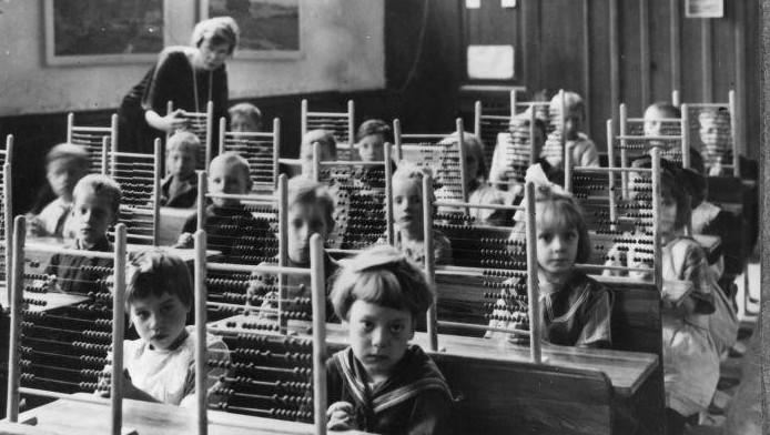Schoolklas poseert met de handen ineengevouwen en telramen op tafel, circa 1930.